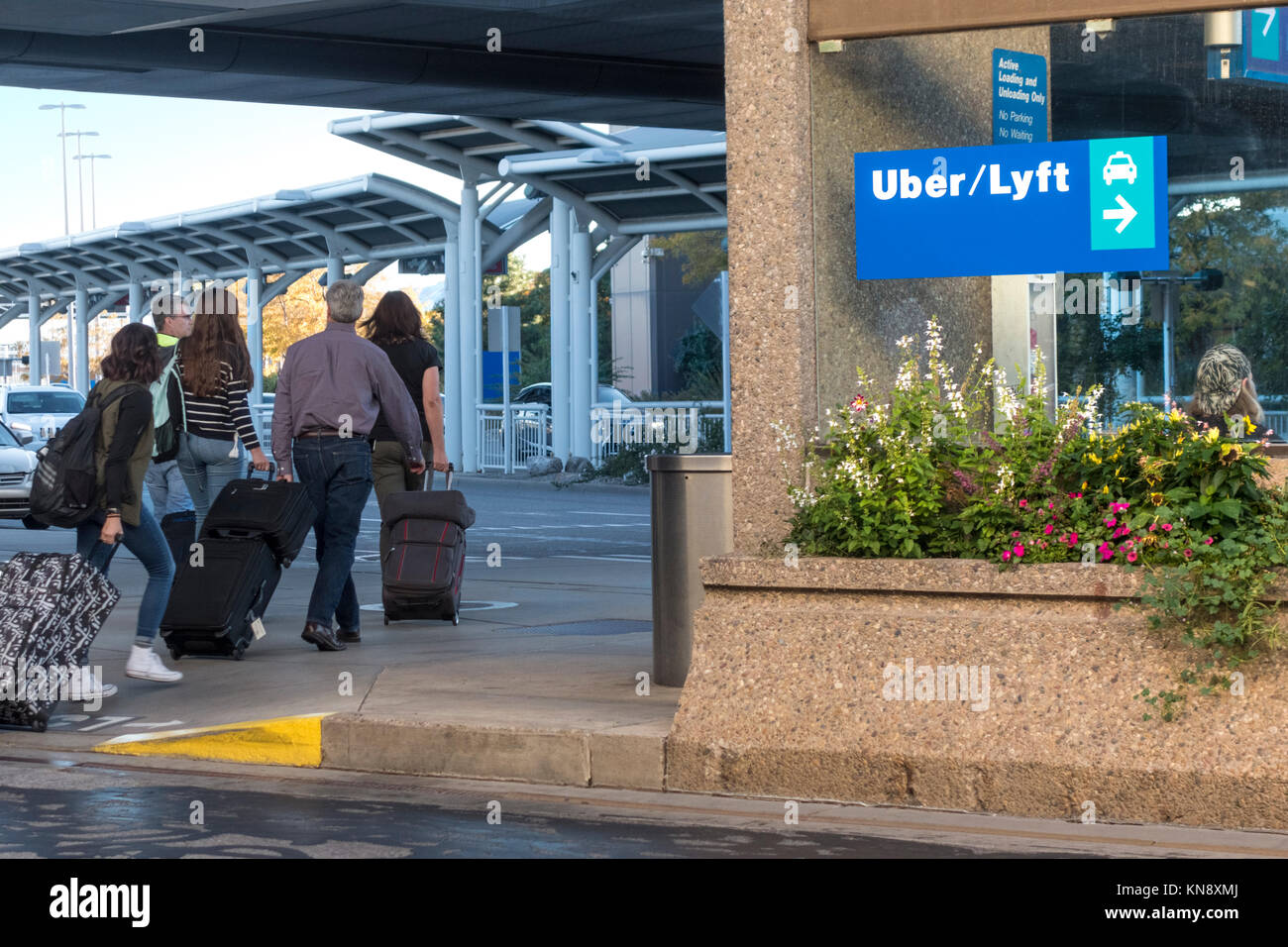 Lyft Uber taxi rank sign at Salt Lake City International Airport. Passengers with luggage. - Stock Image