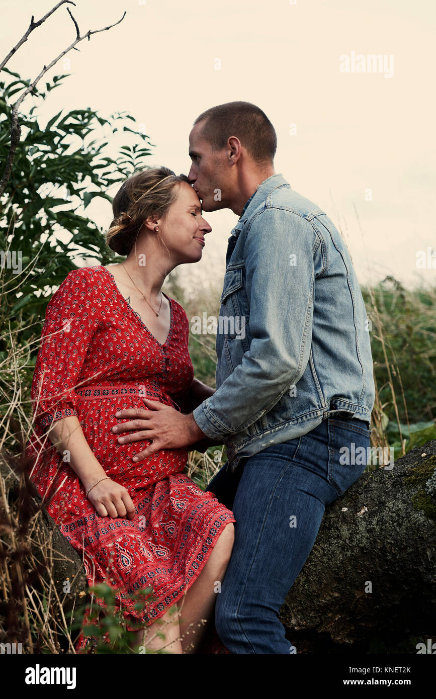 Romantic man kissing pregnant wife's forehead on tree trunk - Stock Image
