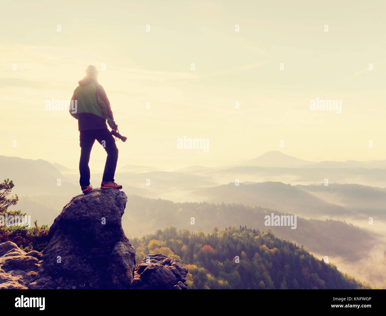 Nature photographer in the action.  Man silhouette above a misty clouds,  morning hilly landscape. - Stock Image