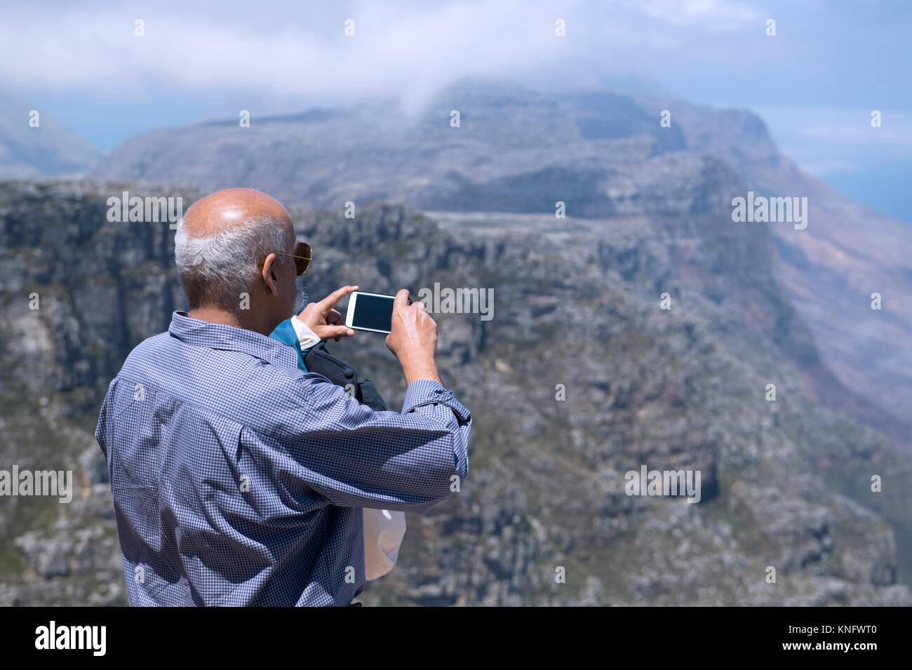Tourist using a mobile phone to take a photograph of the view from the top of Table Mountain in Cape Town, South - Stock Image