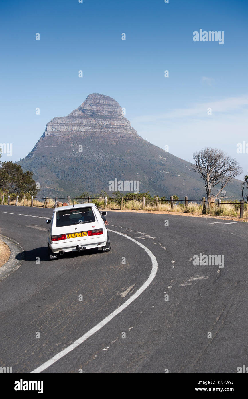 Car driving on the road below Table Mountain in Cape Town, South Africa, with Lion's Head in the distance - Stock Image