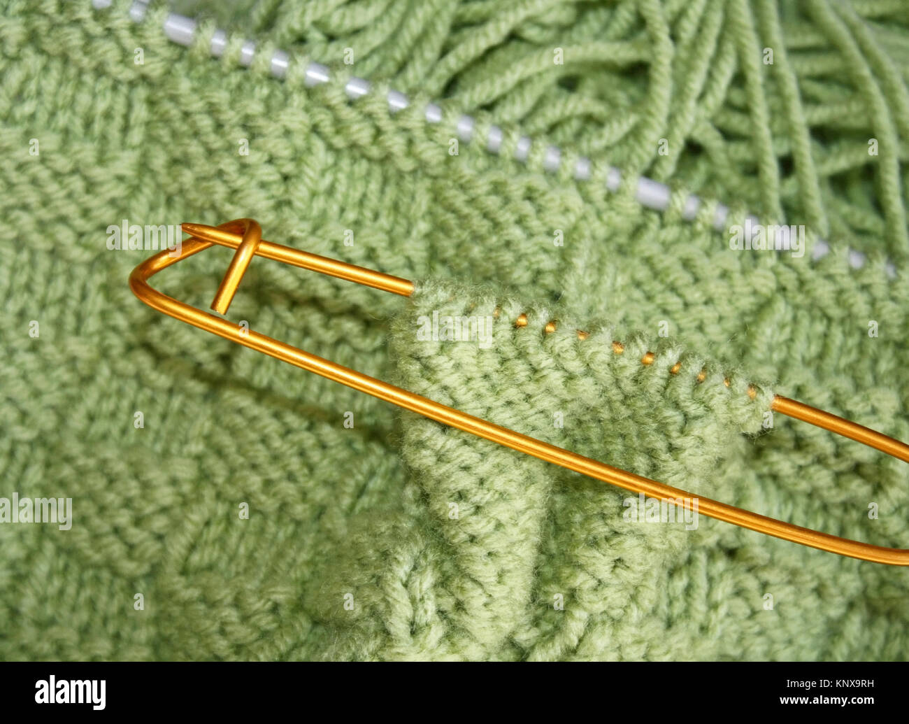 Basket weave pattern knitted on knitting needles in sage green color wool.   Stitch holder in place marking off - Stock Image