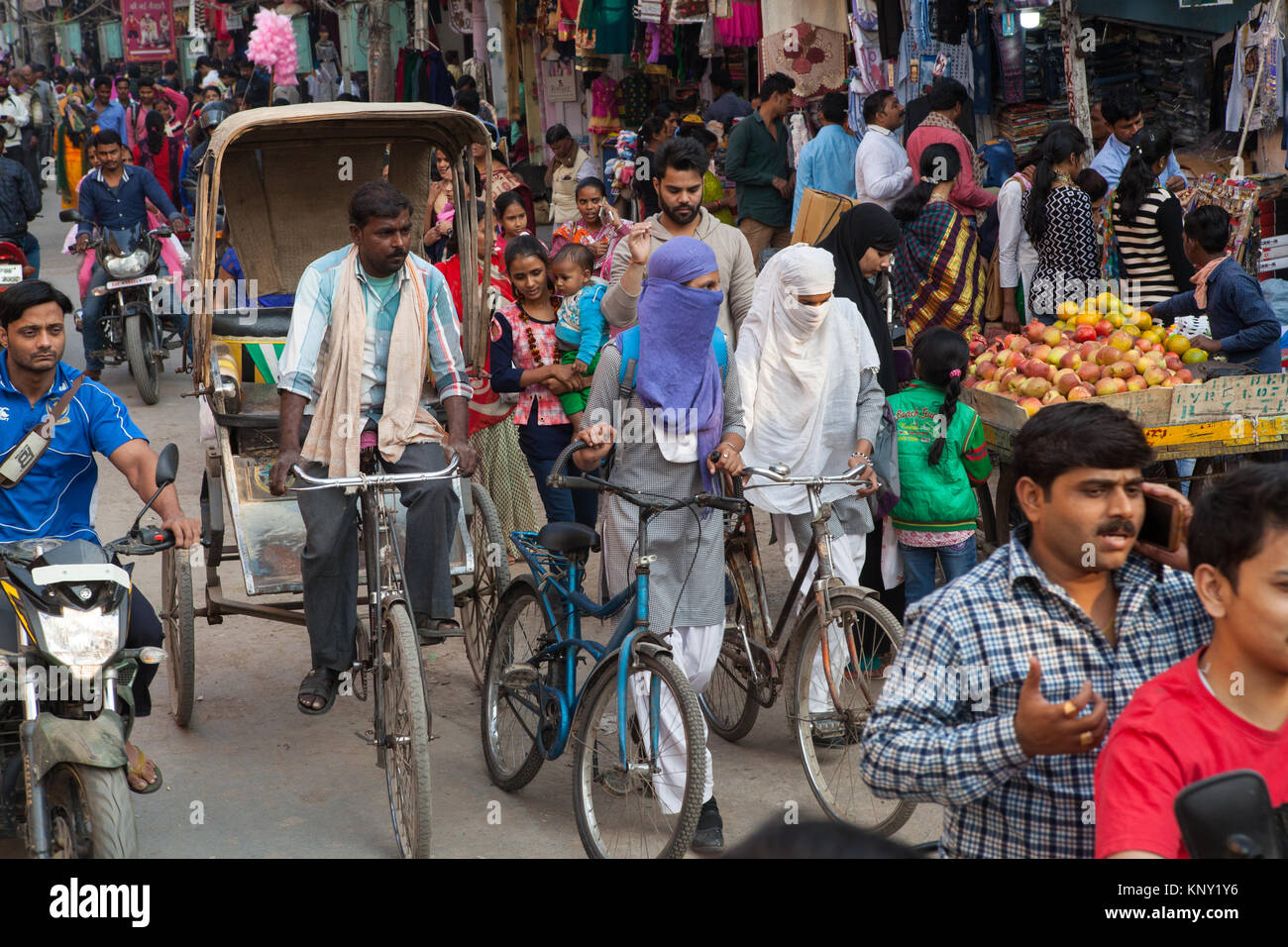 A rickshaw cyclist and two muslim women pushing bicyles through a busy and congested Dasashwamedha Ghat Road  in - Stock Image