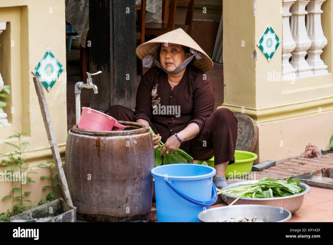 Woman washing vegetables in Vietnam, My Tho, Mekong Delta river area. Vinh Trang Pagoda complex. - Stock Image