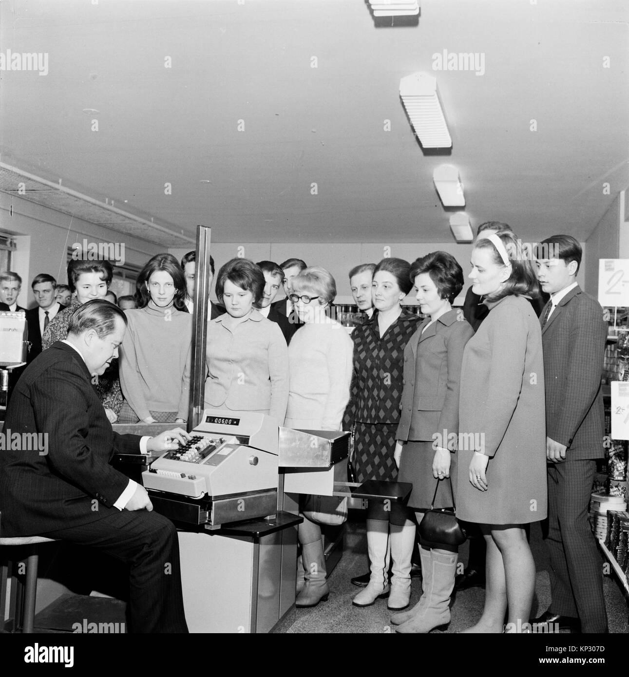 Man demonstrating use of modern cash register till watched by shop staff, Helsinki, Finland, 1960s - Stock Image