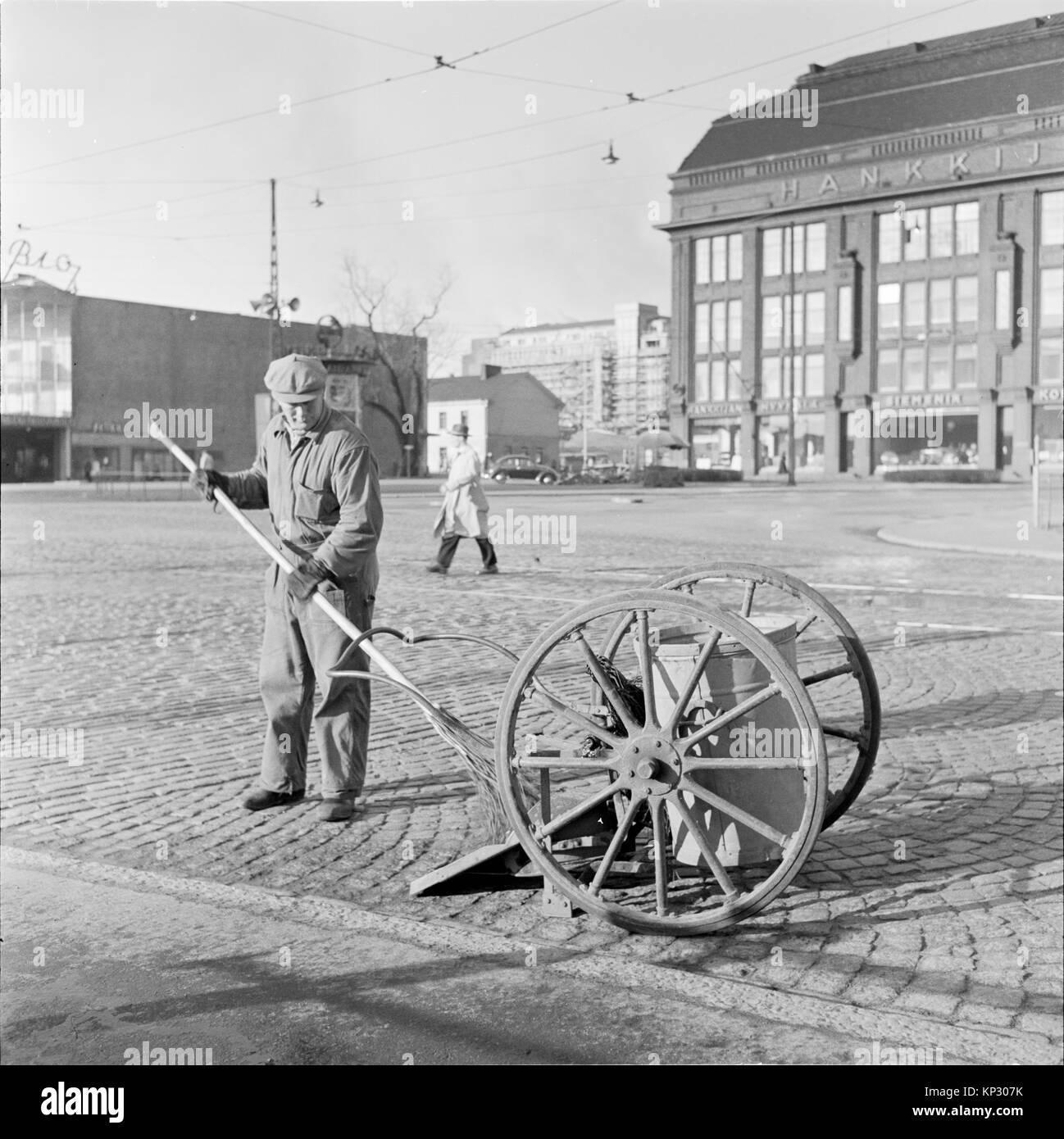 Male cleaner worker sweeping street Helsinki, Finland 1995 - Stock Image