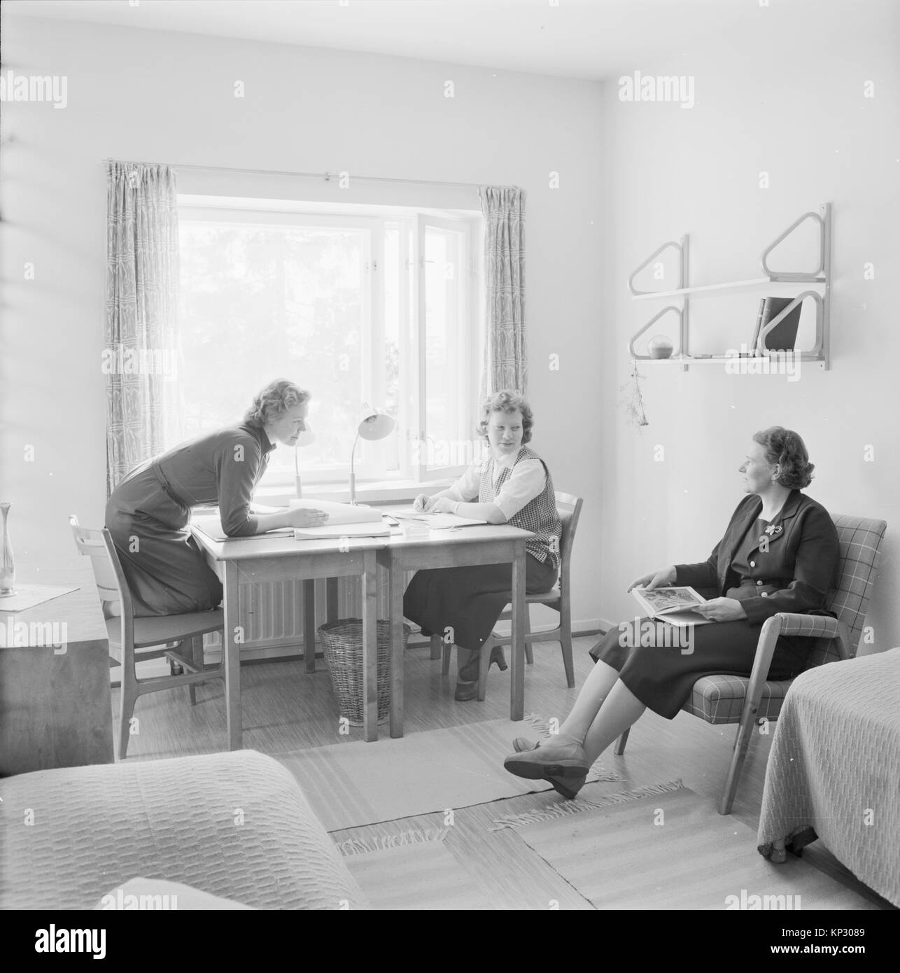 Two female students at boarding school in a dormitory room with adult woman housemistress teacher, Helsinki, Finland, - Stock Image