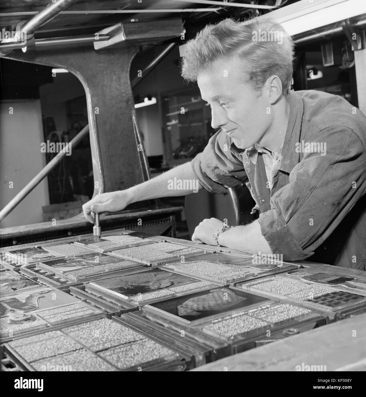Male print worker working with printing press typeset, Helsinki, Finland, 1957 - Stock Image