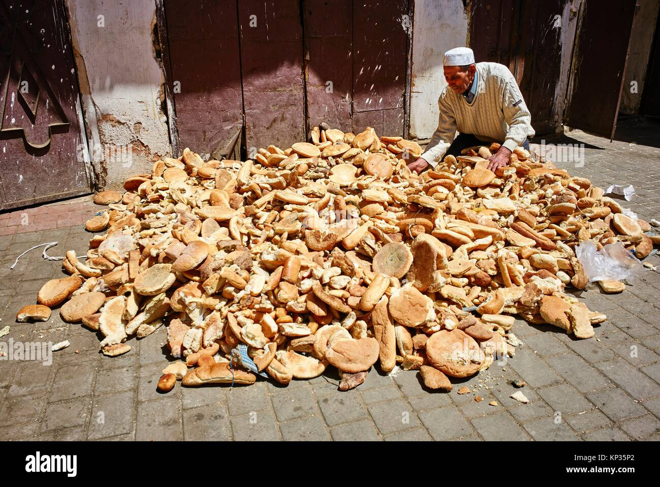 Gathering stale bread at the street market in Meknes, Morocco - Stock Image