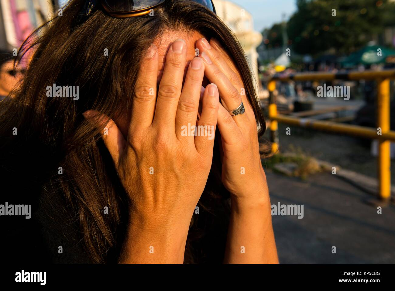 Tilburg, Netherlands. Streetportrait brunette woman covering her face with both hands, being shy. - Stock Image