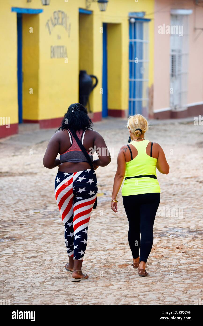 Woman wearing plant designed with the colors of the U. S flag walk in a street of Trinidad, Cuba. - Stock Image