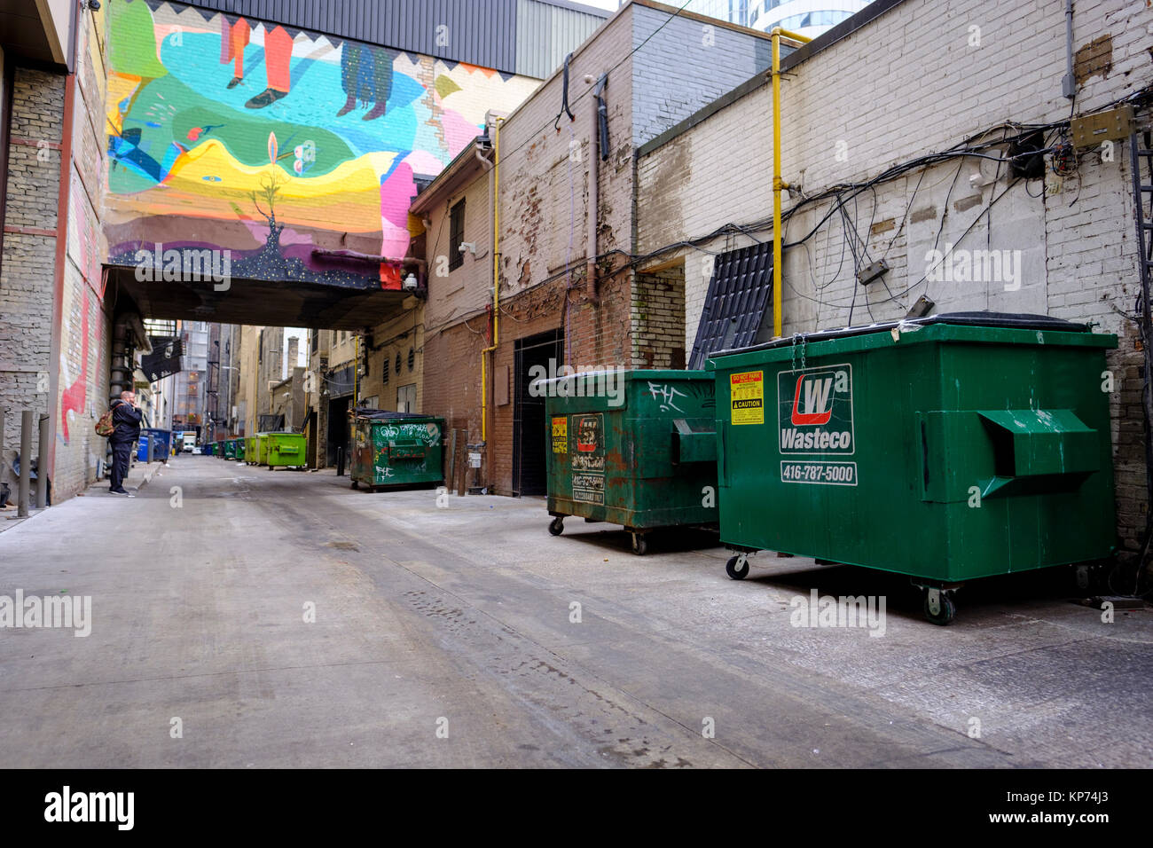 O'Keefe Lane alleyway with many green garbage dumpsters lined up against the wall, man smoking, graffiti art - Stock Image