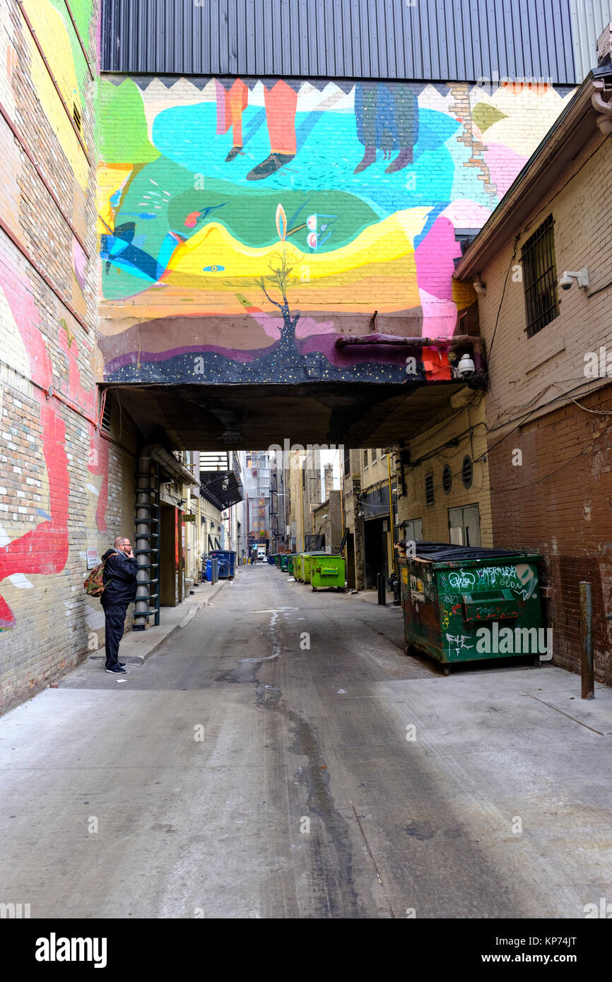 O'Keefe Lane alleyway with many green garbage dumpsters lined up against the wall, man smoking, graffiti artwork, - Stock Image