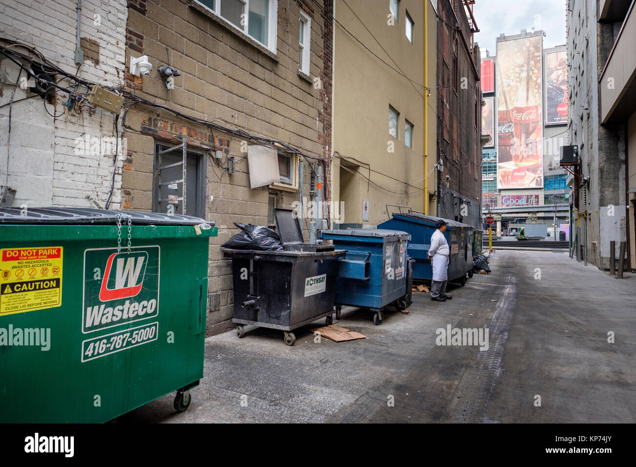 O'Keefe Lane alley on Dundas Square, garbage dumpsters lined up against the wall, man on work break, Coca-Cola - Stock Image