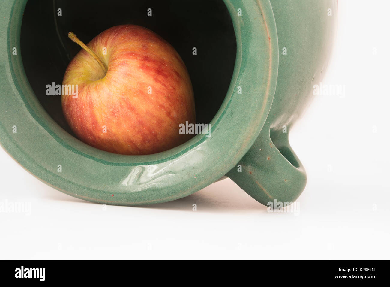 close up view of a red apple inside the greenish earthen jar - Stock Image