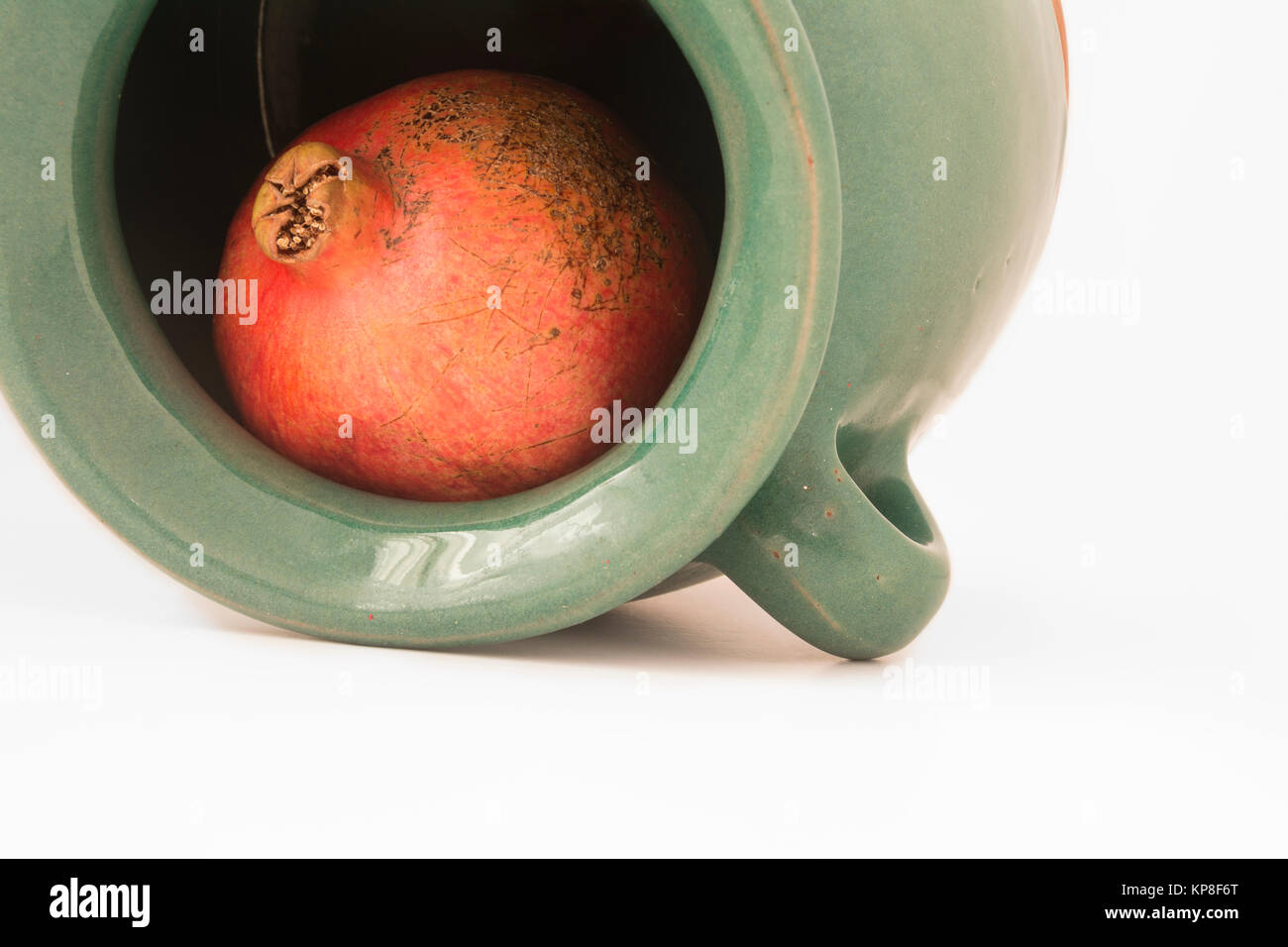close up view of a red pomegranate inside the greenish earthen jar - Stock Image