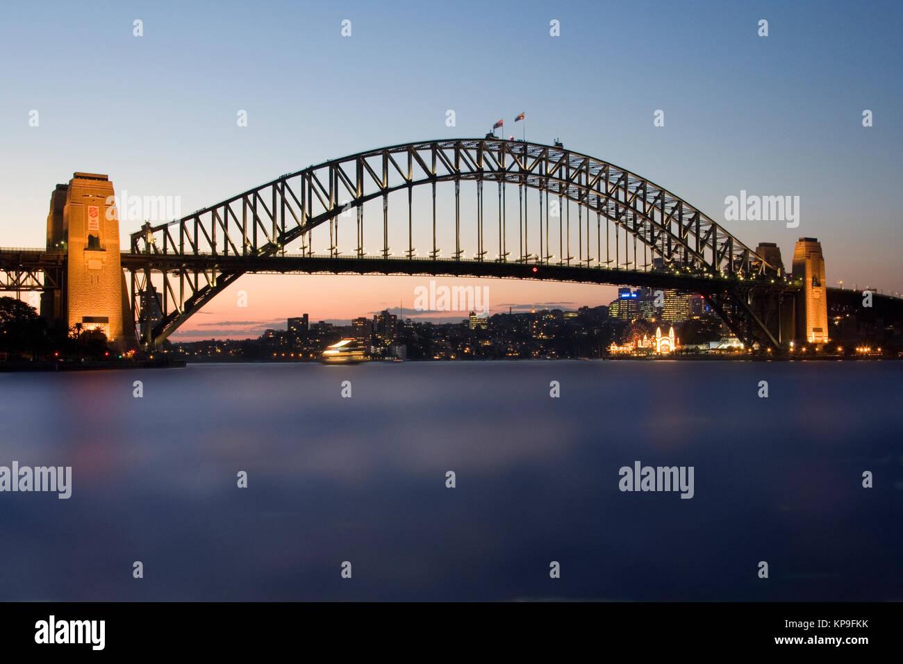 Sydney Harbor Bridge in Sydney Harbor, New South Wales, Australia. Opened in 1932, it carries rail, road traffic, - Stock Image