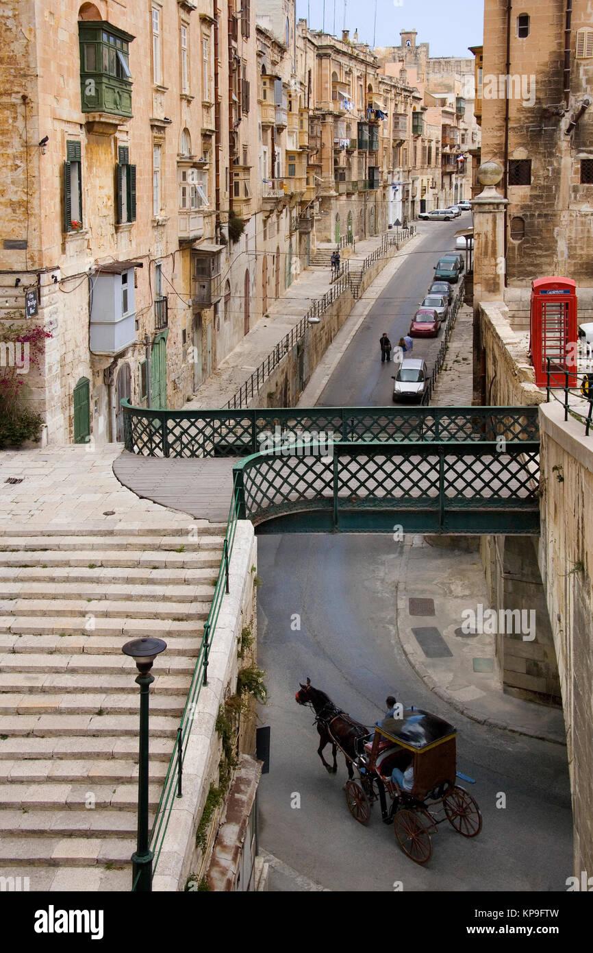 Street in the city of Valletta on the Mediterranean island of Malta. British style telephone box. - Stock Image