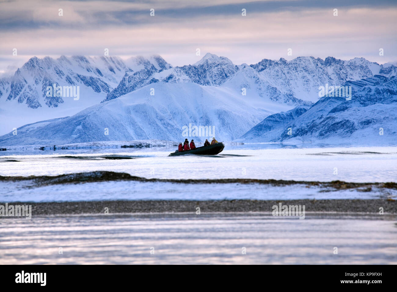 Adventure tourists on a zodiac in Raudfjord on the Svalbard Islands (Spitsbergen) in the High Arctic. - Stock Image