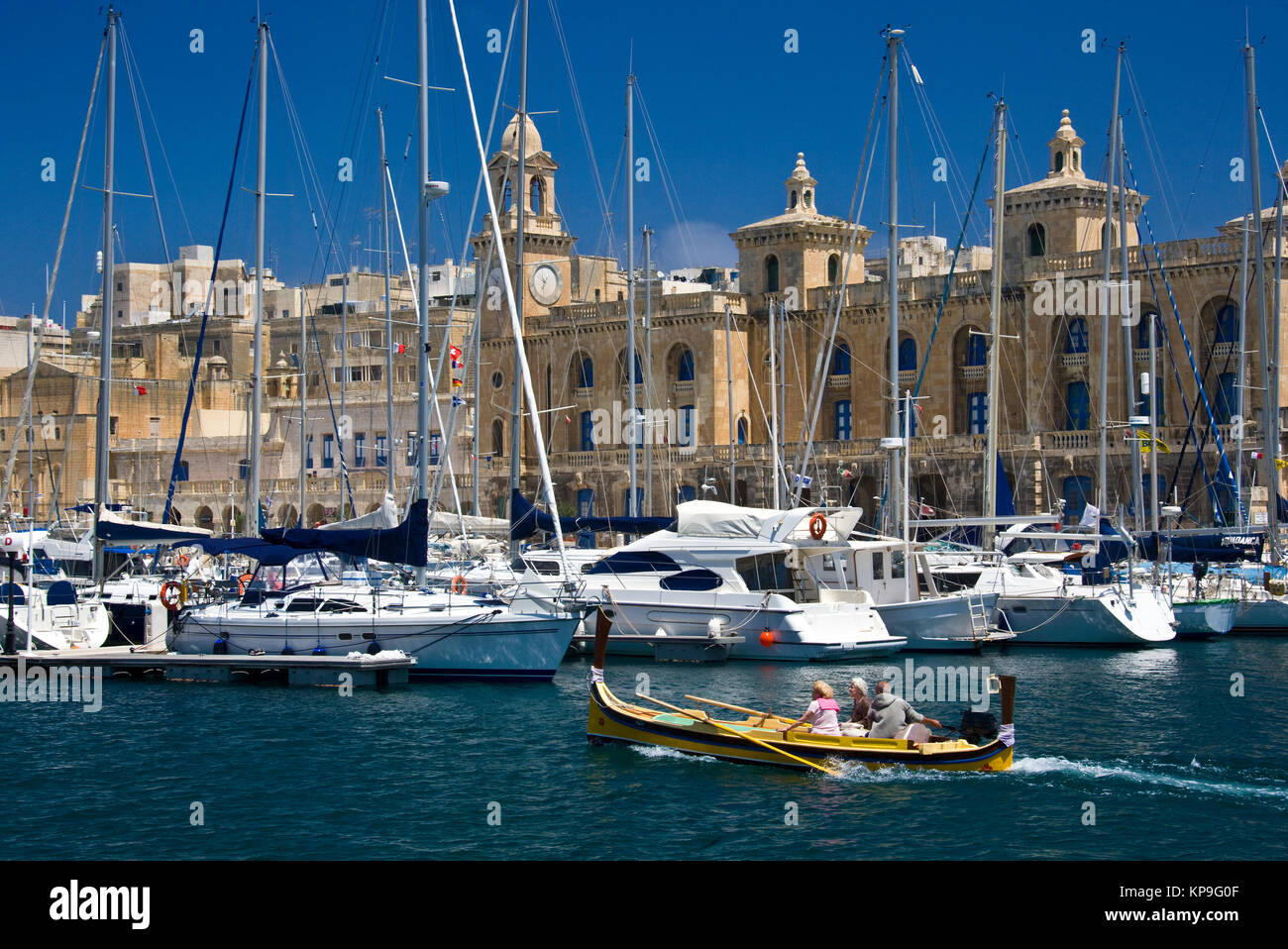 A traditional Maltese Lazzu fishing boat passing the Maritime Museum and marina at Vittoriosa in Valletta on the - Stock Image