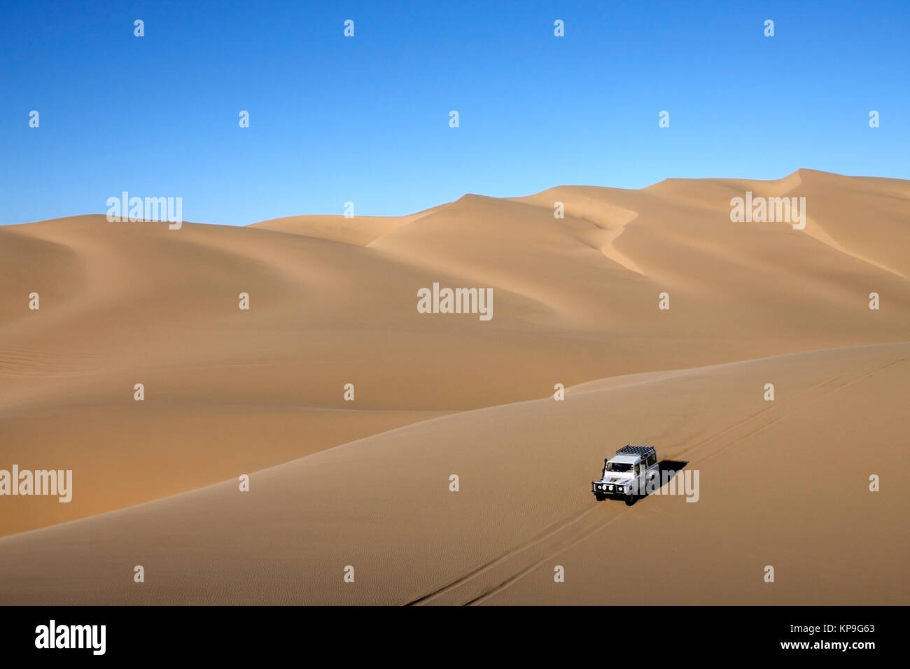 Vehicle drving over sand dunes in the Namib Desert of Namibia. - Stock Image