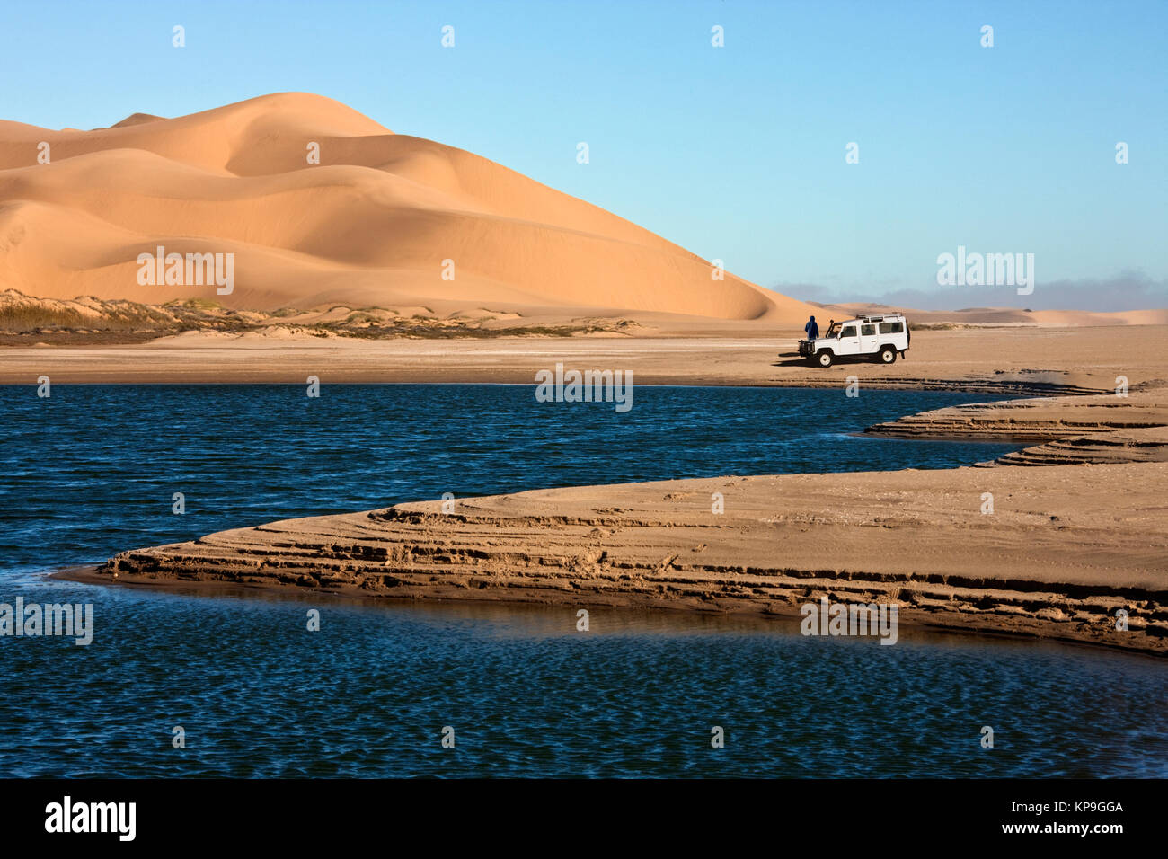 Adventure tourists with vehicle in the Namib Desert in Namib-Nuakluft National Park near Sandwich Bay on the coast - Stock Image