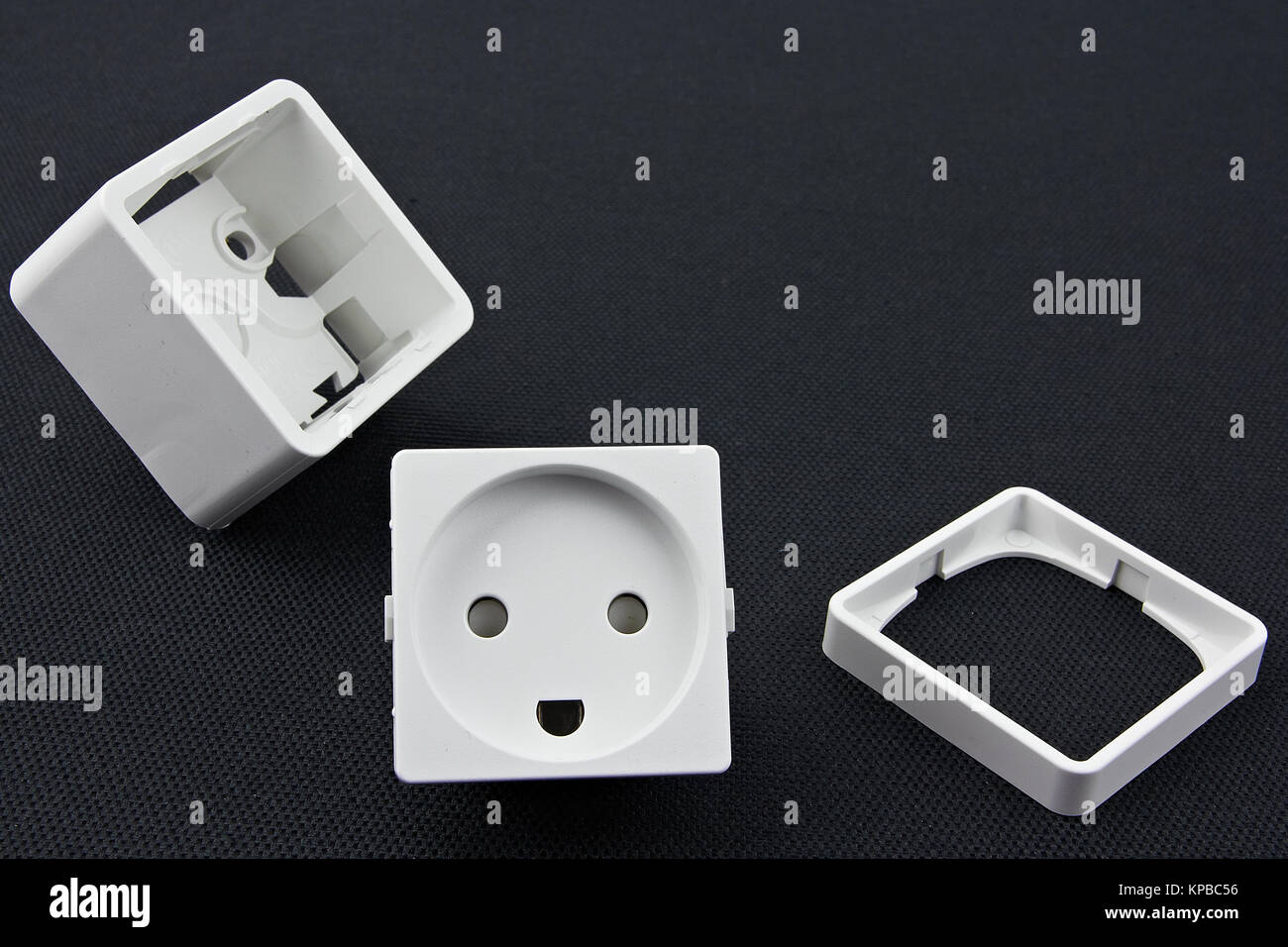 Dismantled electrical outlet lying on a black surface - Stock Image