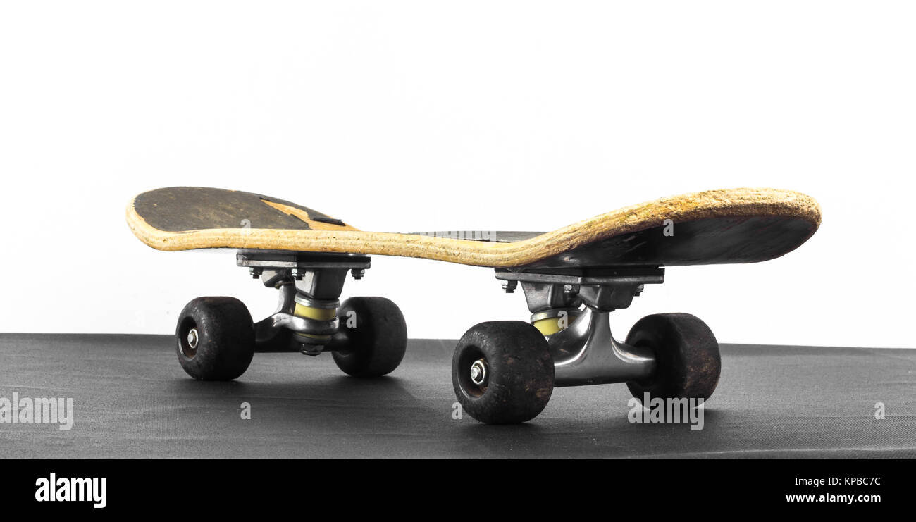 Old skateboard on black and white background - Stock Image