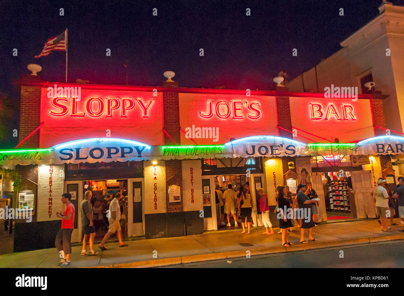 Sloppy Joe's Bar on Duval Street at night with neon lights and tourists. Key West, Florida - Stock Image