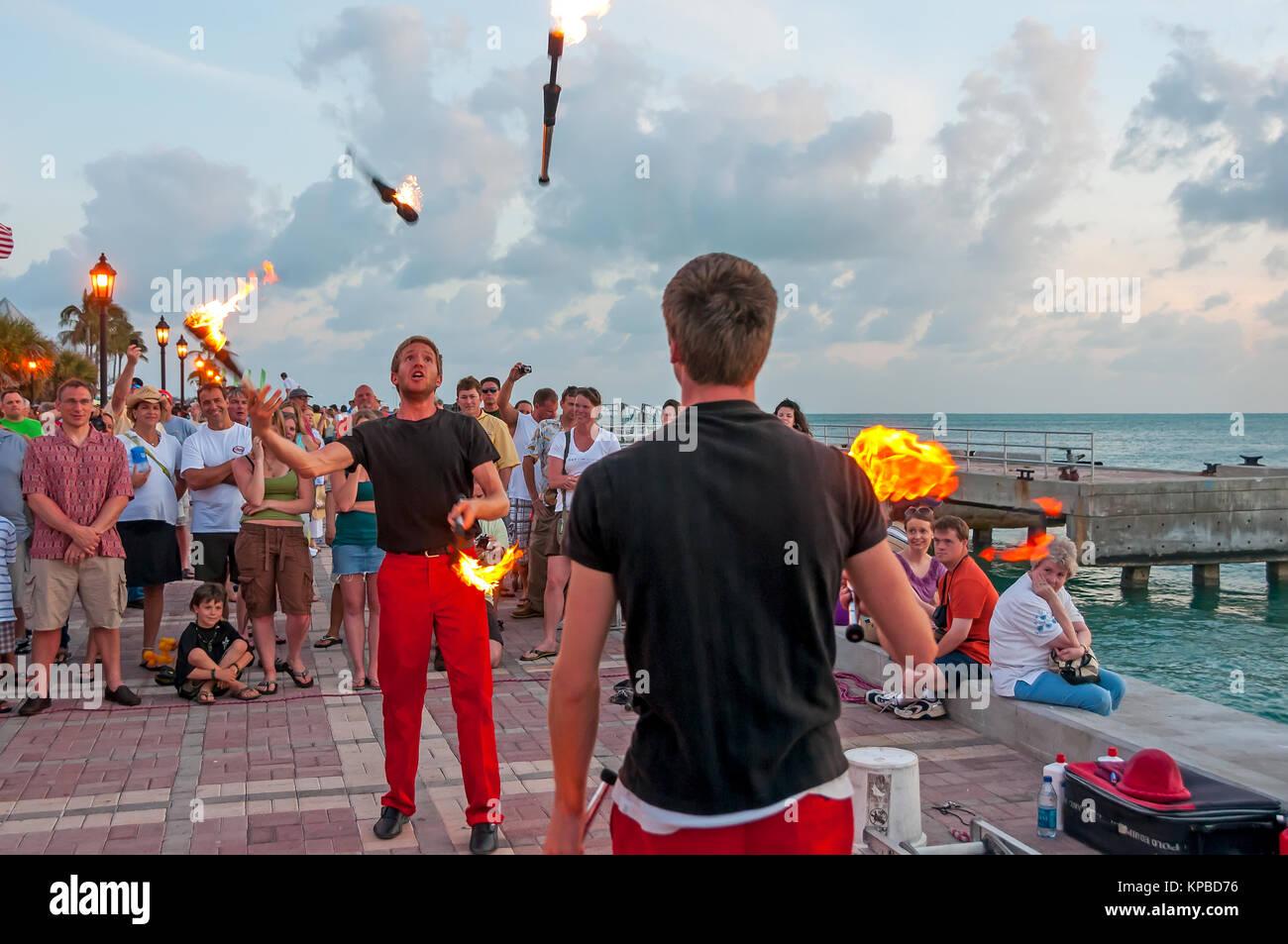 Jufflers with fire batons perform at Mallory Square Sunset Celebration, Key West, Florida - Stock Image