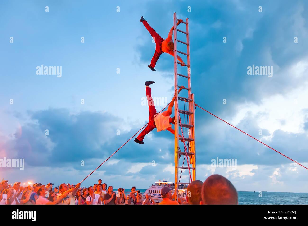 Acrobats on ladder perform vertical stand at Sunset Celebration Key West Florida - Stock Image