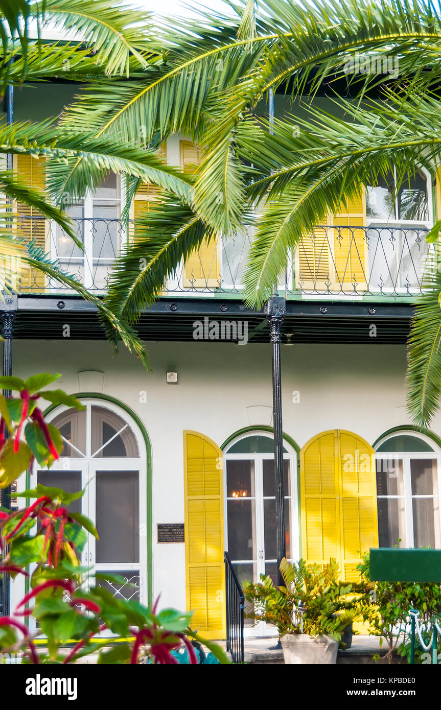 Ernest Hemingway Home & Museum yellow shutters, balcony and palm trees, Key West, Florida - Stock Image