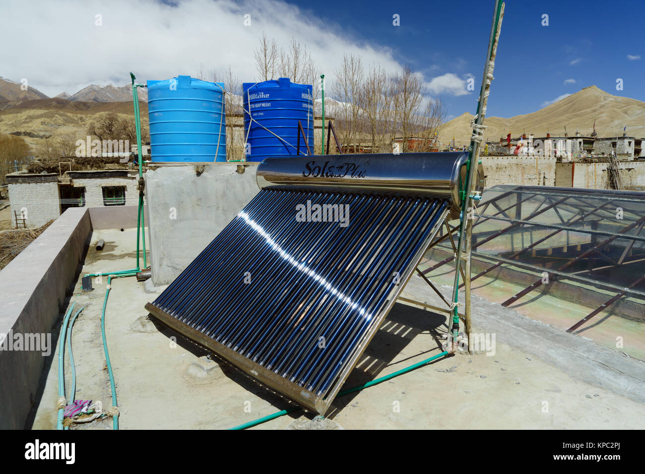 Solar water heater collector and tanks on the roof of a guesthouse in Lo Mantang, Upper Mustang region, Nepal. - Stock Image