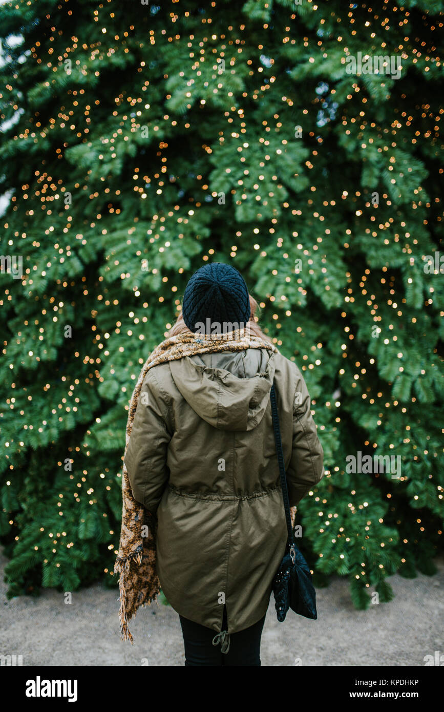 Woman standing in front of big Christmas tree - Stock Image
