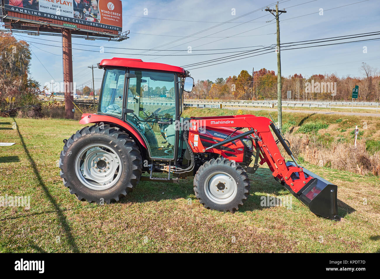 Brand new Mahindra 2565 CL shuttle cab red tractor sitting in front of the dealership with optional front loader. - Stock Image