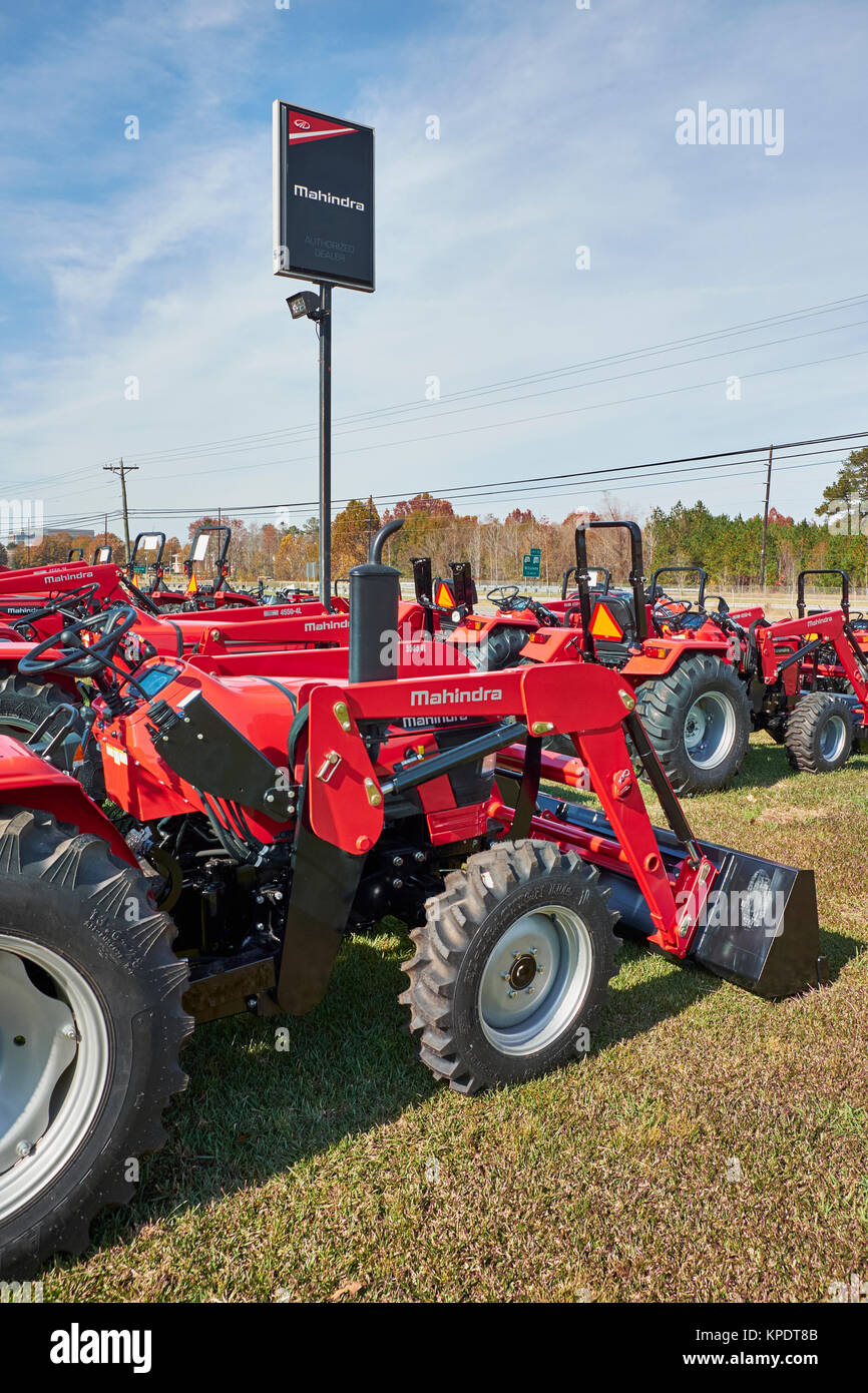 Mahindra dealership sign or signage stands over rows of new red Mahindra farm and construction tractors, all for - Stock Image