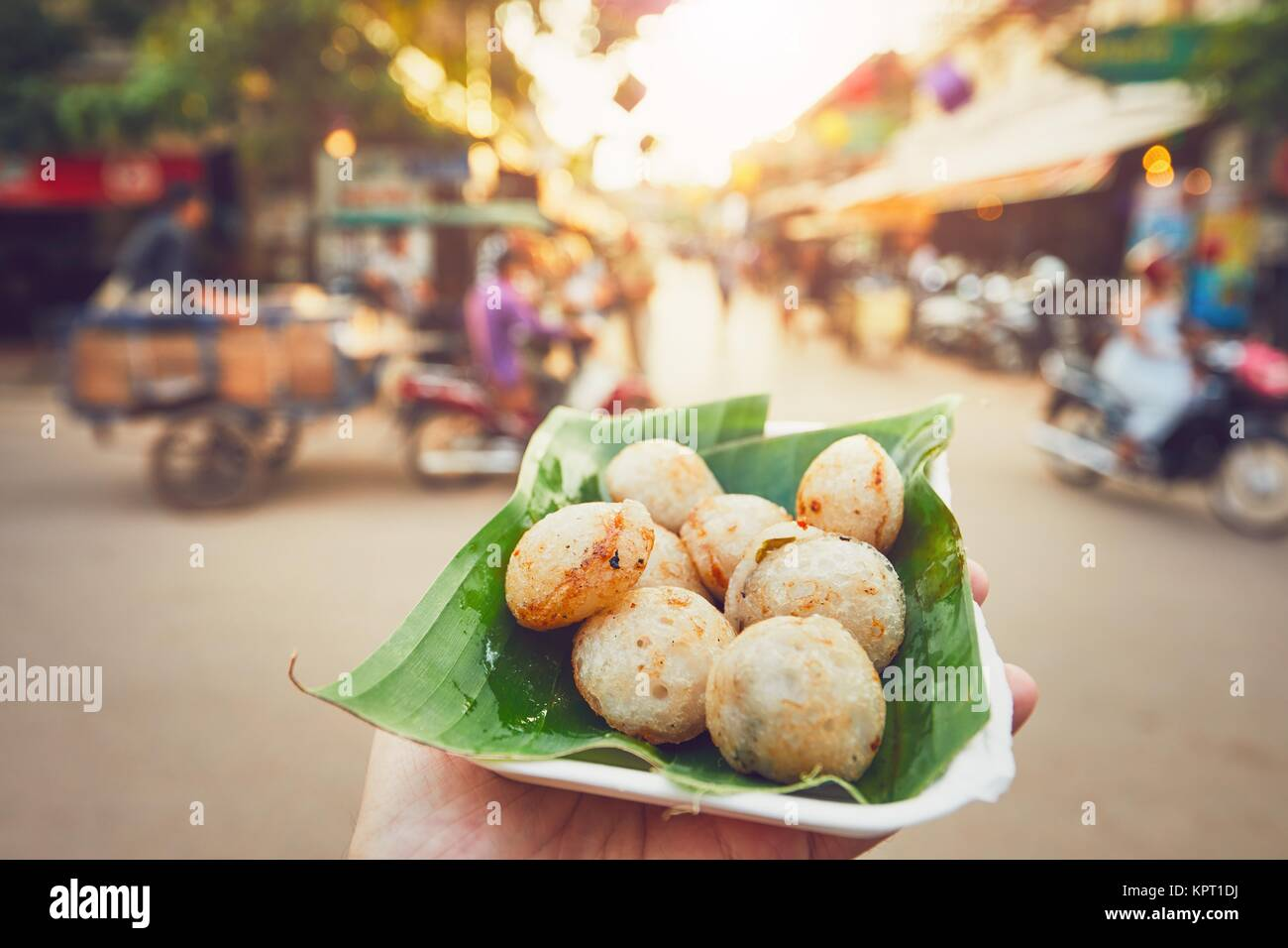 Hand of man holding bowl with sweet coconut food. Busy street full of restaurants, bars and shops - Siem Reap, Cambodia - Stock Image