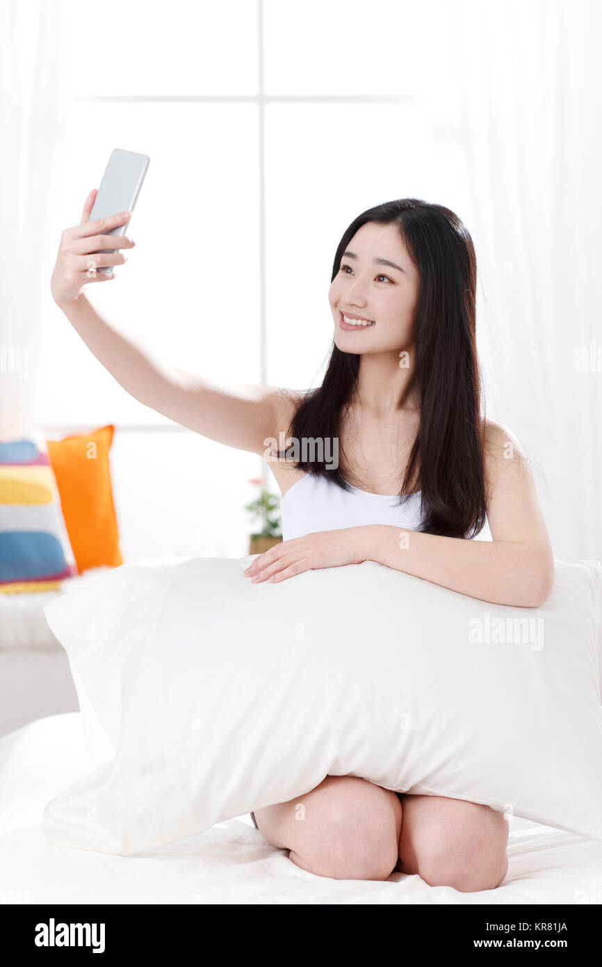 Young women in the bedroom self timer - Stock Image