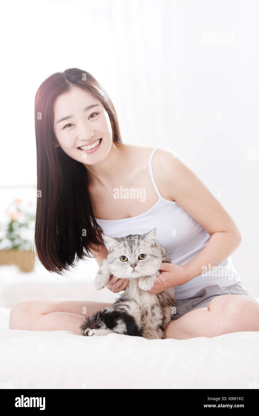 Young women and kittens are in the living room - Stock Image