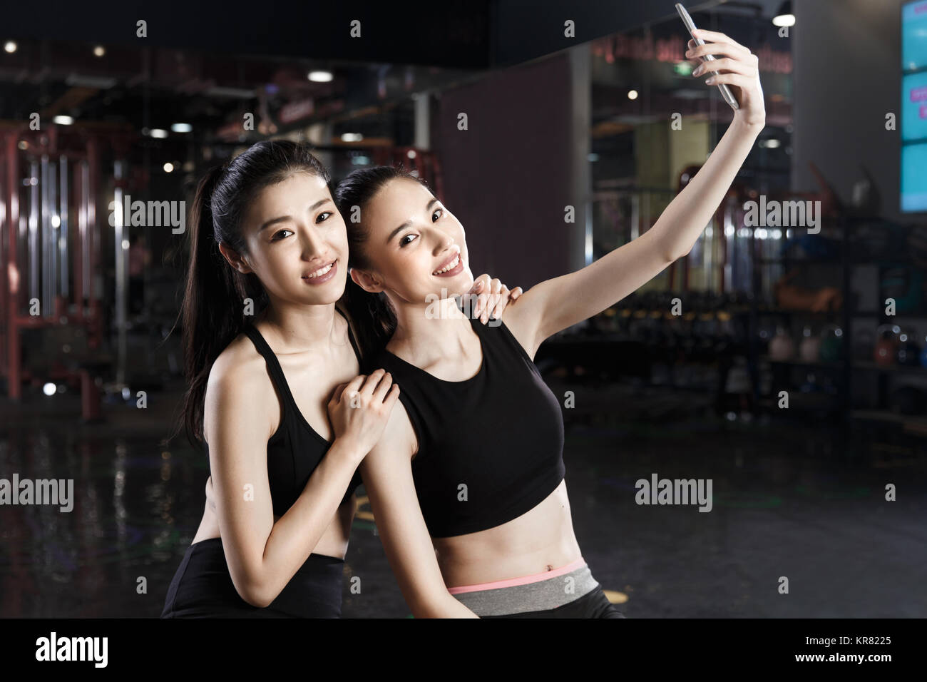 Young women take cell phone self timer in gym - Stock Image