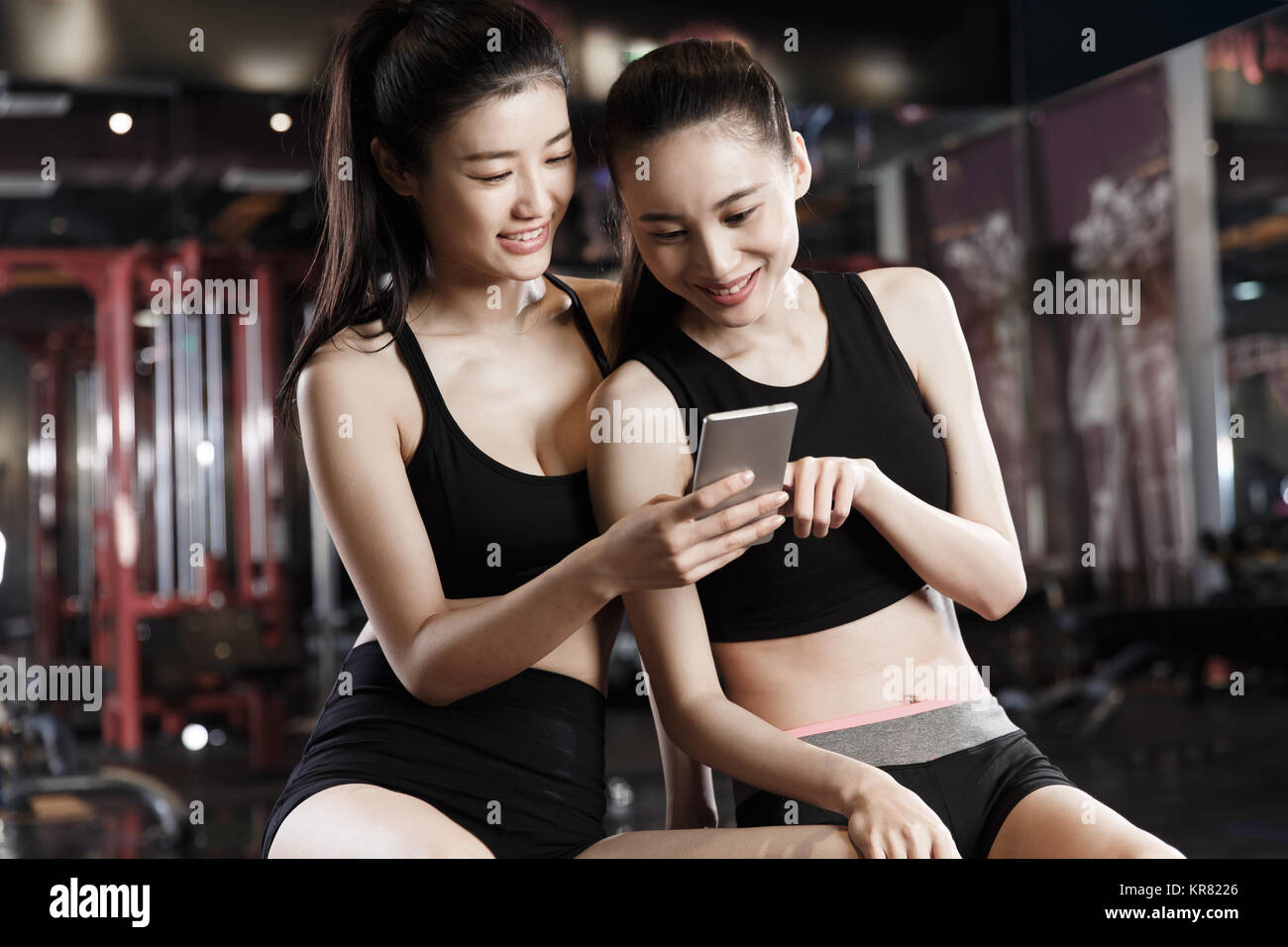 Young women watch mobile phones in the gym - Stock Image