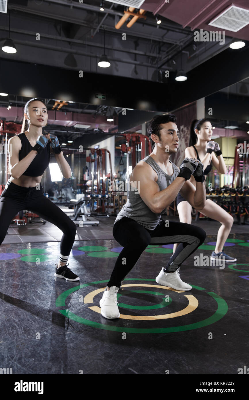 Young people exercise at the gym - Stock Image