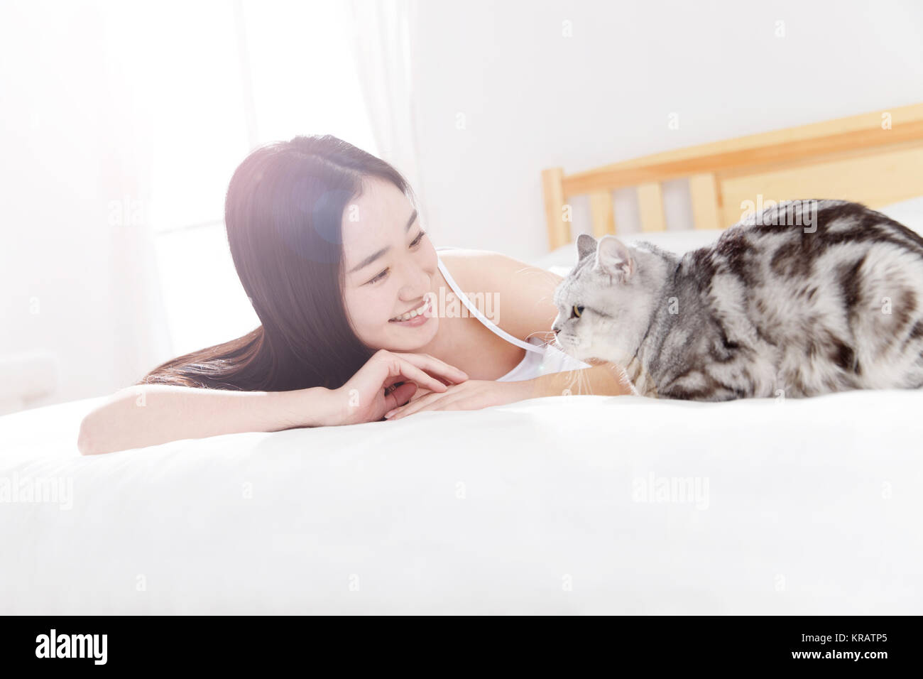 Young women and kittens are in the bedroom - Stock Image