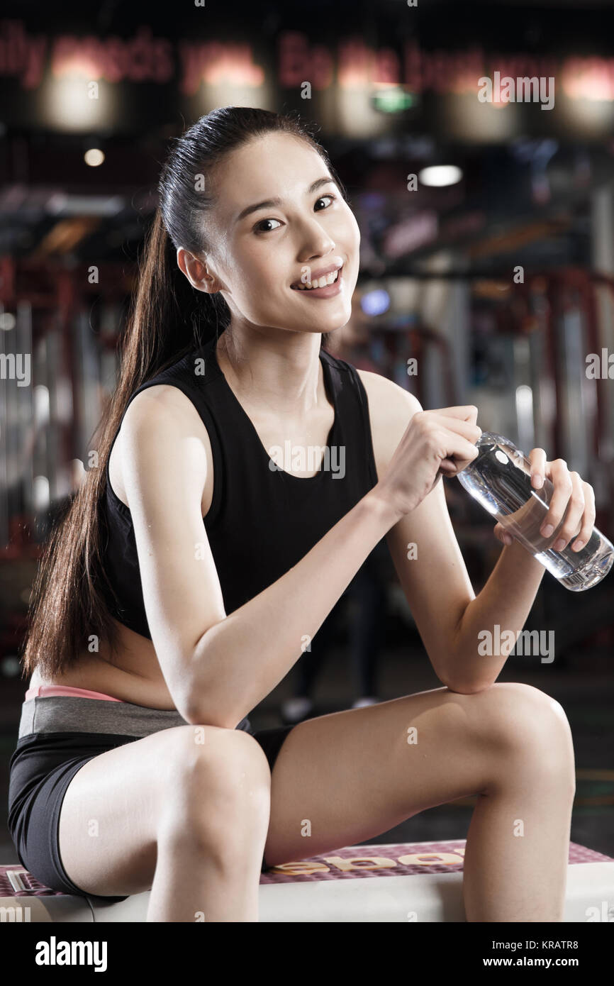 Young women drink water at the gym - Stock Image