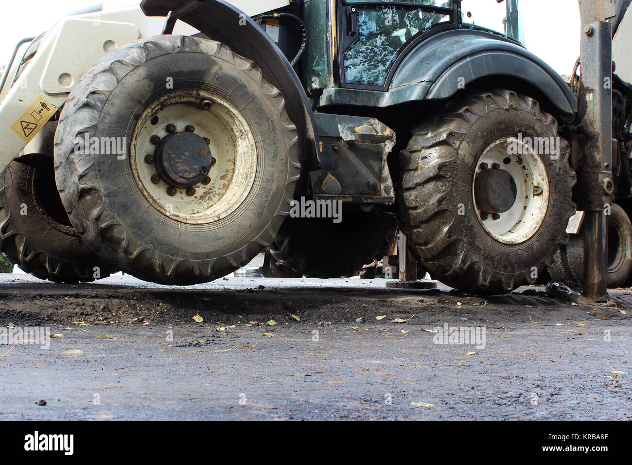 Truck strong outrigger stabilizing legs extended. Tractor on extended outriggers for better stability, digging a - Stock Image
