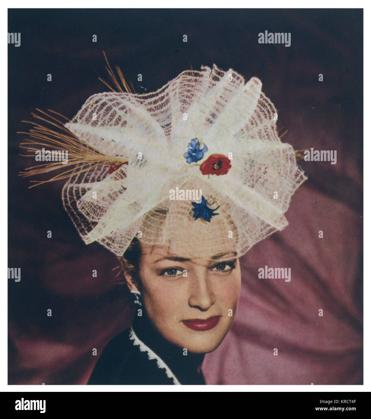 Outlandish net hat decorated with flowers and straw worn by a very brave young woman! Date: August 1946 - Stock Image