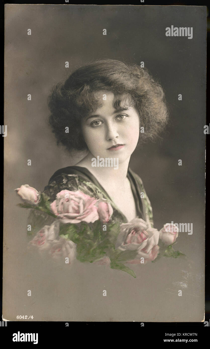 Beautiful young lady with pink roses. Date: circa 1910 - Stock Image