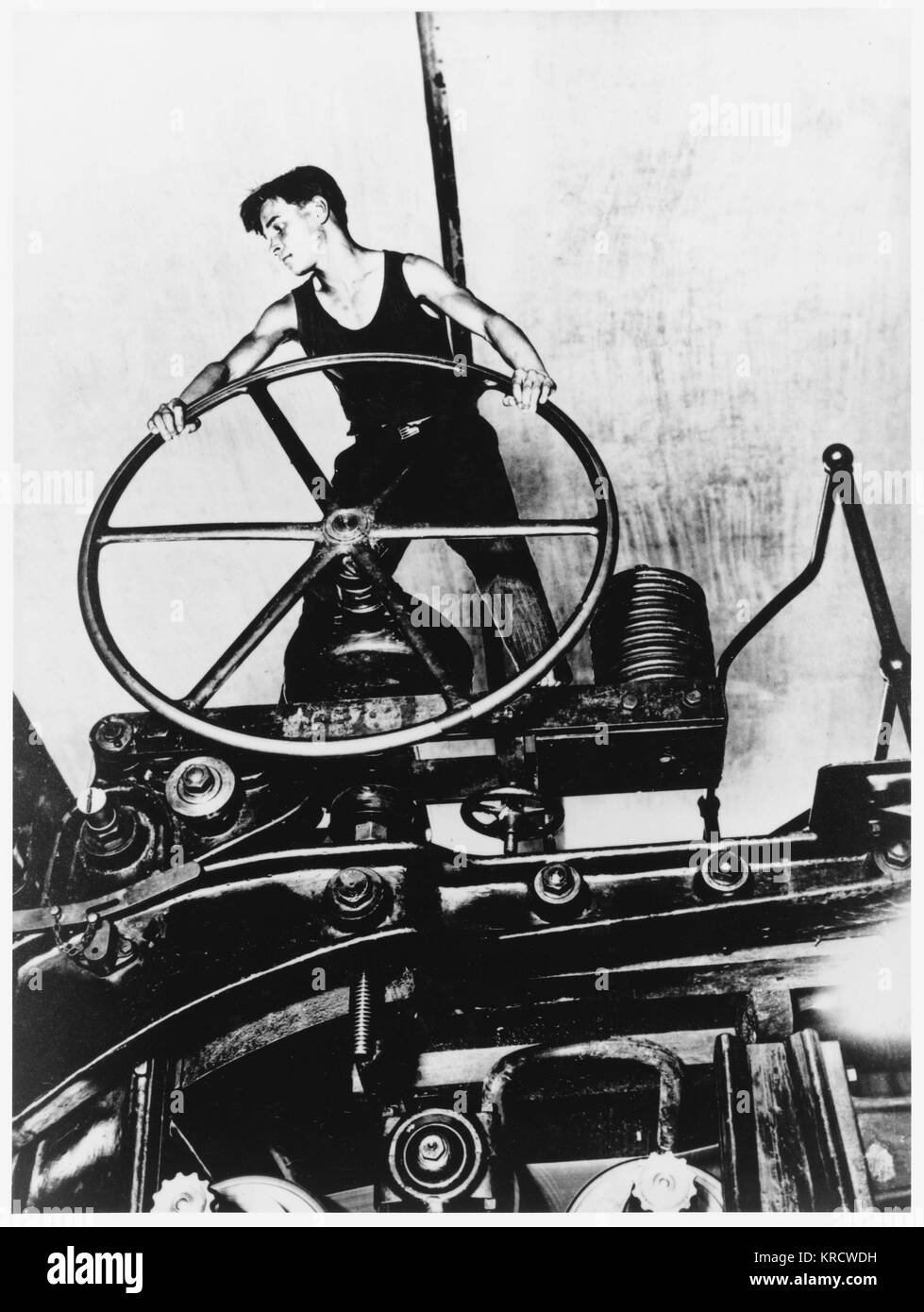 A young man, the ideal of the heroic communist worker, working at a complicated piece of machinery in a cellulose - Stock Image