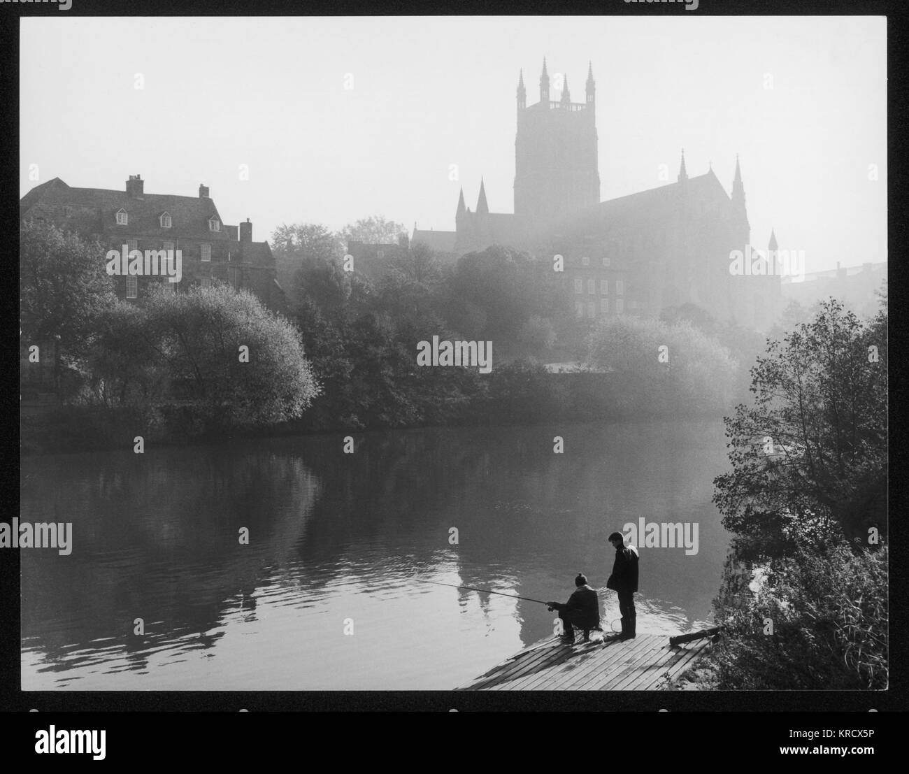 Angling in the River Severn on a misty morning, while  the sun rises behind  Worcester Cathedral in the  distance. - Stock Image