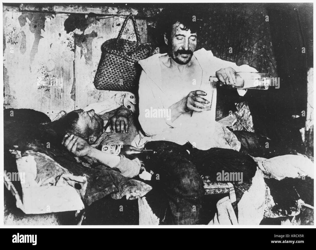 A pair of Russian drunks  imbibe strong drink in  a hovel.        Date: early 20th century - Stock Image